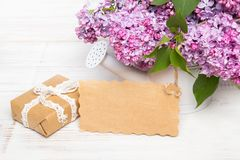 Lilac flowers, gift box and emty card. On white wooden background, copy space stock image