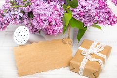 Lilac flowers, gift box and emty card on white wooden background,. Copy space stock photography