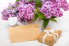Lilac flowers, gift box and emty card on white wooden background. Copy space stock image