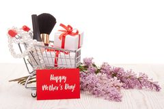 Lilac flowers and gifts on shopping trolley. Shopping trolley with gift boxes and brenches of Lilac on a wooden table on white background. Greeting card Stock Photo