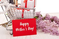 Lilac flowers and gifts on shopping trolley. Shopping trolley with gift boxes and brenches of Lilac on a wooden table on white background. Greeting card Royalty Free Stock Photography