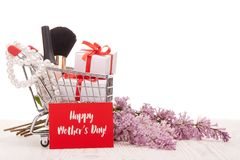 Lilac flowers and gifts on shopping trolley. Shopping trolley with gift boxes and brenches of Lilac on a wooden table on white background. Greeting card Royalty Free Stock Image