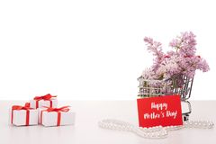 Lilac flowers on shopping trolley and gifts. Shopping trolley with brenches of Lilac, pearl beads and gift boxes  on white background. Copy space for adding Royalty Free Stock Photos