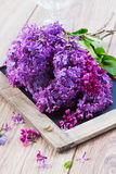 Lilac flowers on table. Twigs of fresh lilac flowers on wooden table Stock Images