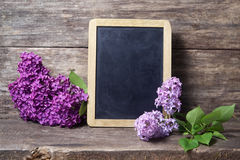 Lilac flowers in a vase and blackboard Royalty Free Stock Image