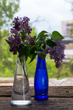 Lilac flowers in vase on the wooden window sill.  Stock Photo