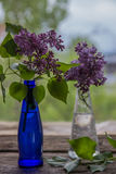 Lilac flowers in vase on the wooden window sill.  Royalty Free Stock Photo