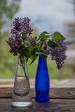 Lilac flowers in vase on the wooden window sill.  Stock Photos
