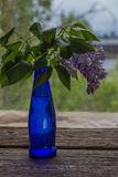 Lilac flowers in vase on the wooden window sill.  Royalty Free Stock Images