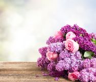Lilac flowers. Violet Lilac flowers with pink roses close up on wooden table, copy space on gray bokeh background Royalty Free Stock Images