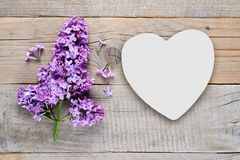 Lilac flowers and white heart. On old wooden background Stock Images