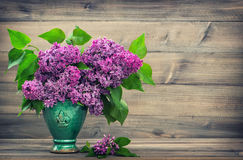 Lilac flowers on wooden background. Vintage style Stock Photos