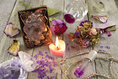Lilac fragrances with picture. Still life with burning candle, lilac fragrances and picture in metal frame Royalty Free Stock Images