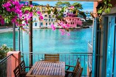 Lilac fuchsiakleurig bloesembloem over hotelveranda voor turkoois kleurde baai van Middellandse Zee en mooi stock fotografie