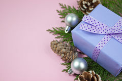 Lilac gift with polka dot ribbon on pink. Lilac gift with polka dot ribbon and Christmas decoration with pine cones on pink stock images