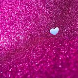 Lilac glitter abstract background with a cut out heartshaped. Abstract glittery textured background with a heartshaped cutout hole conceptual background stock photo