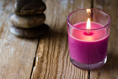 Lilac lavender candle and a stack of balanced zen stones in the background, on wood surface, copyspace for text, harmony Stock Photos