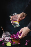 Lilac lemonade water with lemon. Female hands hold glass of lilac lemonade with lemon. Glass jar of sugared lilac flowers and vintage bowl of fresh flowers on stock image