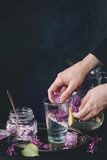 Lilac lemonade water with lemon. Female hands put ice cubes with flowers into glass of lilac lemonade with lemon. Glass jar of sugared lilac flowers and pitcher royalty free stock images