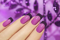 Lilac manicure. Lilac manicure on female hand with purple sparkles Royalty Free Stock Photos