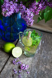 Lilac and mint tea. Lilac flowers and fresh mint tea on the wooden table Royalty Free Stock Image