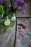 Lilac and mint tea. Lilac flowers and fresh mint tea on the wooden table Stock Images