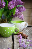 Lilac and mint tea. Lilac flowers and fresh mint tea on the wooden table Royalty Free Stock Photo