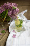 Lilac and mint tea. Lilac flowers and fresh mint tea on the wooden table Stock Photography