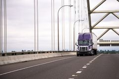 Lilac modern big rig semi truck with trailer moves along the arc. A modern purple large big rig semi truck with a dry van semi trailer for the transport of Royalty Free Stock Photography