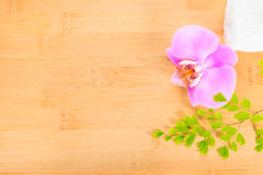 Lilac  orchid, green branch and towels on bamboo Royalty Free Stock Photo