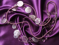 Lilac pearls on a lilac silk as background Stock Images