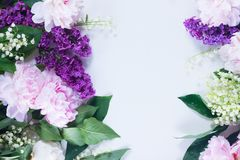Lilac, pink peonies and lilly of the walley. Floral flat lay scene - lilac, peonies and lilly of the walley flowers on white background with copy space Royalty Free Stock Images