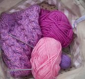 Lilac, pink and purple tangles of threads lie in a basket on a pink background. royalty free stock photo