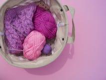 Lilac, roze en purpere verwarring van draden ligt in een mand op een roze achtergrond royalty-vrije stock afbeelding