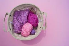 Lilac, roze en purpere verwarring van draden ligt in een mand op een roze achtergrond royalty-vrije stock foto's