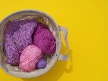 Lilac, roze en purpere verwarring van draden ligt in een mand op een gele achtergrond De favoriete hobby is creatief stock afbeeldingen