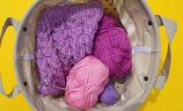 Lilac, roze en purpere verwarring van draden ligt in een mand op een gele achtergrond De favoriete hobby is creatief royalty-vrije stock afbeelding