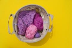 Lilac, roze en purpere verwarring van draden ligt in een mand op een gele achtergrond De favoriete hobby is creatief stock foto's