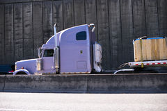 Lilac semi truck and concrete wall fence road Stock Photography