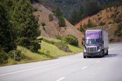 Lilac semi vrachtwagen met aluminiumaanhangwagen beweegt zich langs het winden h Royalty-vrije Stock Foto's