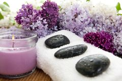 Lilac spa. Three rocks on a white towel with flowers on a bamboo mat. Focus on third rock. Shallow DOF Royalty Free Stock Photos