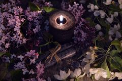 Lilac spring flowers with burning black candle. Occult, esoteric and divination still life. Halloween background with vintage objects and magic ritual Stock Photos