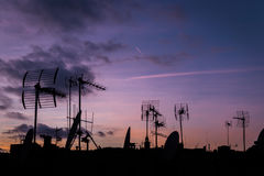 Lilac sunset and many silhouettes of roofs with antennas, Barcel Royalty Free Stock Images
