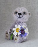 Lilac teddy-bear a bunch of flowers Royalty Free Stock Images