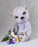 Lilac teddy-bear with a bunch of flowers at feet Royalty Free Stock Photos