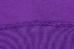 Lilac texture of fabric from a piece of wool with a seam. Lilac fabric background from a piece of woolen clothes with a seam royalty free stock photography