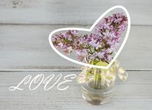 Lilac in a transparent vase on a wooden background, white heart and the inscription love. Template for creative projects Royalty Free Stock Images