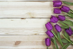 Lilac tulips on planked wooden background from above, holiday de stock photo