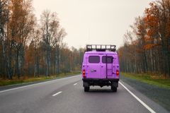 A lilac van driving on a road along the forest.  Royalty Free Stock Photos