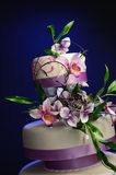 Lilac Wedding cake. Three layered lilac bridal cake decorated with a bouquet of summer flowers; Orchids and Hydrangea, on a blue background. Flowers are all hand Royalty Free Stock Photos
